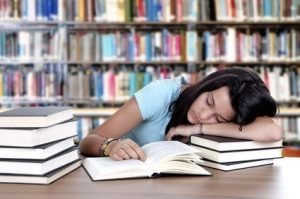female student sleeping in a university library